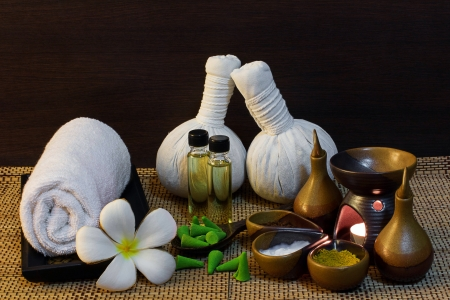 herbal massage ball: Thai spa massage setting with spa mud,  herbal compress balls, essential oil bottle, towel, frangipani and incense cone