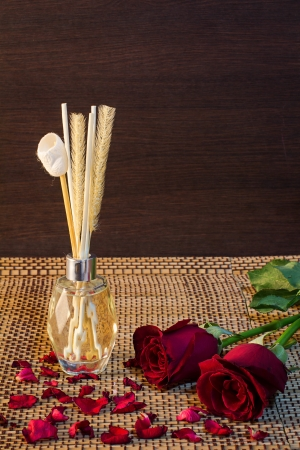 Aroma reed diffuser setting with rose and rose petals on wood pattern backgruond photo