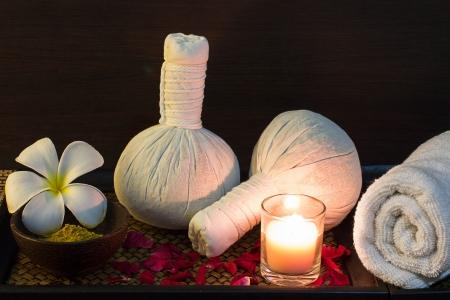herbal massage ball: Thai spa massage setting with towel, frangipani, herbal compress balls and rose petals