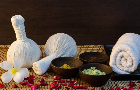 thai spa massage setting with towel, frangipani, herbal compress balls, bath salt and rose petals photo