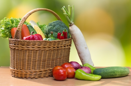 Variety of fresh vegetables in basket on wood table photo