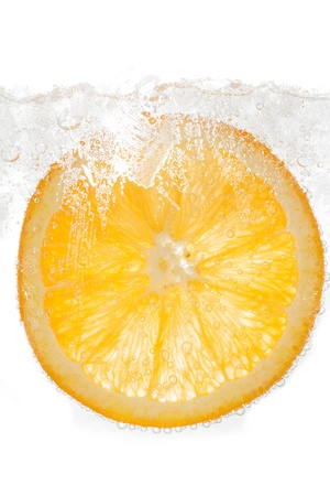 Slice orange in water with bubbles and ice  on white background photo