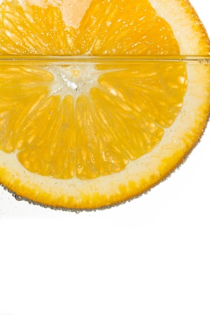 Slice orange in water with bubbles on white background photo