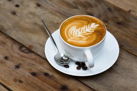 Tazza di caffè caldo latte art sul tavolo in legno