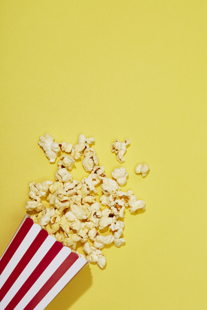 Full of popcorn in classic striped box on color background