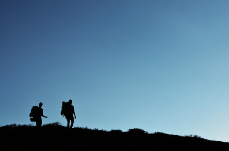 backpackers: silhouette of couple of backpackers hiking on the mountain range in sunset