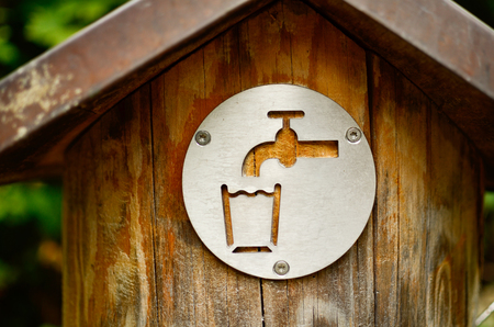 drinking water sign: drinking water sign on a sring tap outdoor in park. the tap is wooden and old. closeup horizontal composition. ecological concept of saving water and natural resources