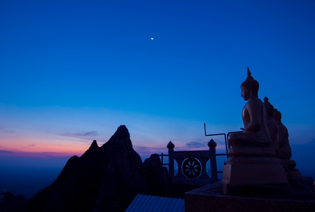 Buddha on the hill top in the early morning at Wat Tam Sau or Tiger cave temple Stock Photo