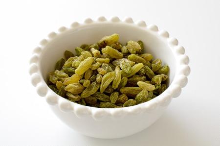 Green raisins in a white bowl Foto de archivo