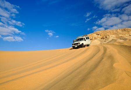 east river: Side view of off all terrain motor car driving across sandy desert