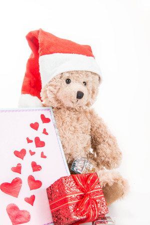 Teddy bear with gift and blank greeting card on white background