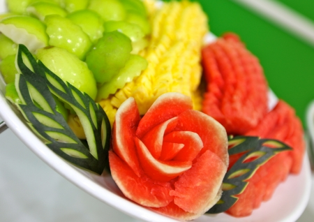 mix carved fruits in plate Editorial