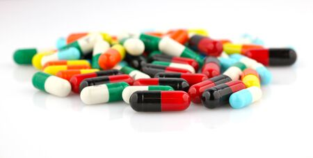 colorful medicine capsules on white photo