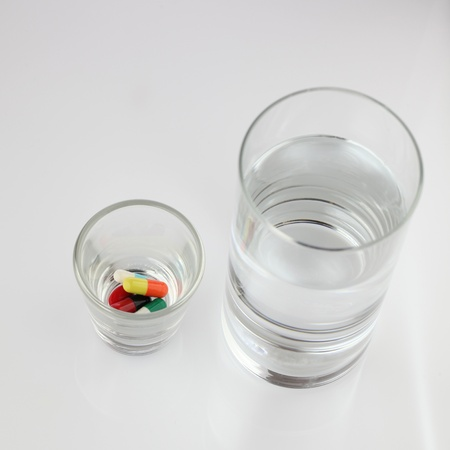medicine capsules and water on white photo