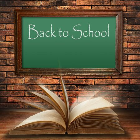 page down: back to school blackboard on brick wall with open old book Stock Photo