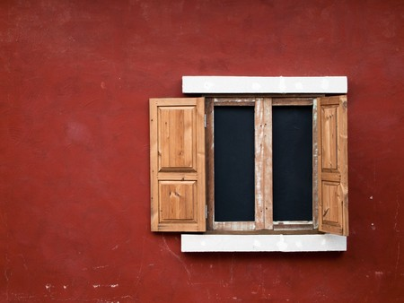 open fake wood window on red wall