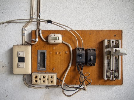 electrical equipment: old dirty Electrical in wood panel on wall Stock Photo