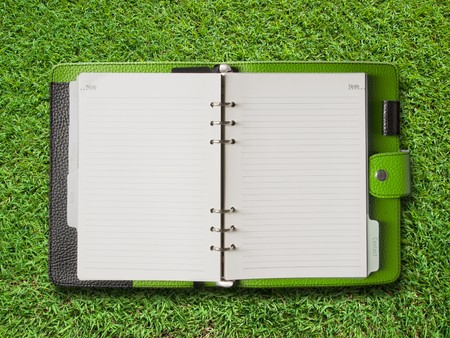Open Green Cover Binder on Green Grass Background photo