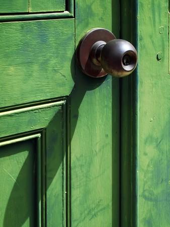 Old iron doorknob on Green wood door photo