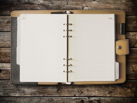 personal organizer: Black and cream leather cover of binder notebook on wood