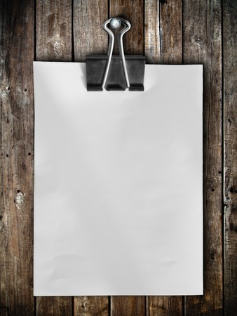 clamp: Black clip and White blank note paper hang on wood panel