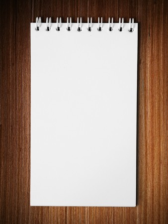 books on a wooden surface: Long blank white note book vertical on wood table background