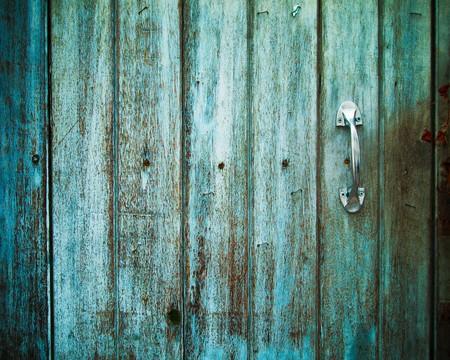 manejar: Antiguo mango de puerta, con una antigua puerta de madera pintada con el color verde