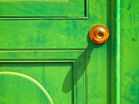 Orange door knob on Old Green wood door photo