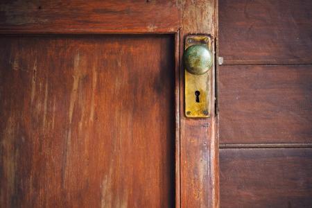 Pomo de la puerta y ojo de cerradura de latón en la antigua puerta de madera