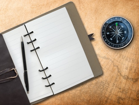 Black pen with Brown Leather cover note book and Compass on old map background photo