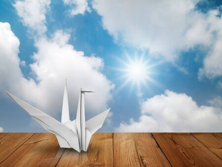 White fold paper bird on wood floor and bright sky with sun photo