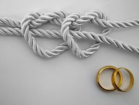 Double heart shaped silver rope tied and a double gold ring photo