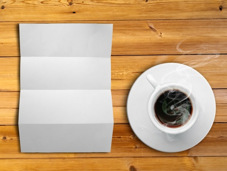 White fold paper and a white coffee cup on a wooden desk