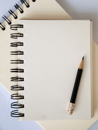 Light cream color paper note book and black pencil on\ white