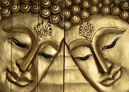 wood carving: Double Buddha faces carved wood gold-painted Stock Photo