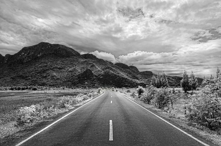 Black and white road to the mountain in Thailand Standard-Bild