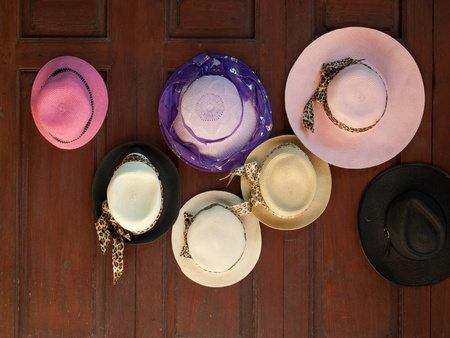 Several multiple hat hanging on wood wall photo