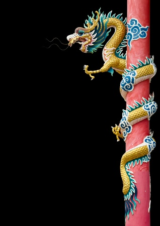 Golden Chinese Dragon Wrapped around red pole on black background photo