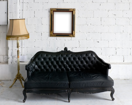 Old black leather sofa with lamp and wood picture frame on white wall photo