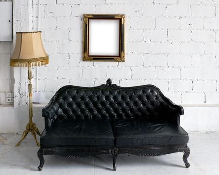 leren bank: Oude zwarte leren bank met lamp en hout fotolijstje op witte muur
