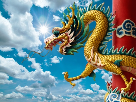 ゴールデン中国ドラゴンを包んだ赤い棒および明るい空