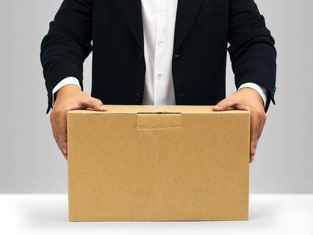 Businessmen in black suit Hold down on the brown paper box photo