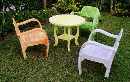 armrest: The three wood chairs with armrest and yellow round table On the grass in the garden