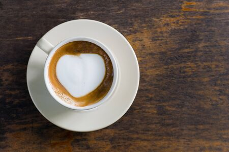 Coffee, cappuccino milk foam heart In a ceramic cup on the table photo