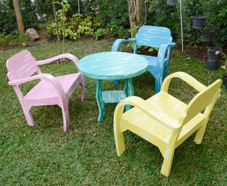 armrest: The three wood chairs with armrest and green round table On the grass in the garden