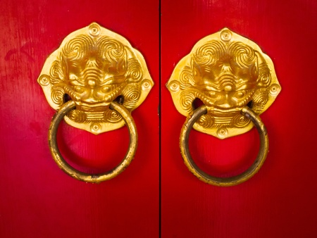 Door handle developing Chinese traditional golden head lion on red wood door