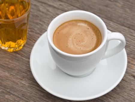 filiżanka kawy: BiaÅ'y ceramiczny kubek kawy i szklankÄ™ herbaty na stole Wood