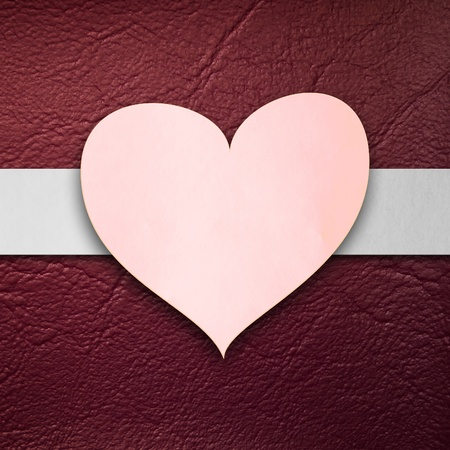Pink paper heart form on Red Leatherette texture photo