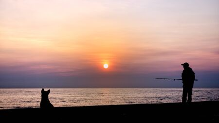 Silhouette of the fishing and dog by the sea in the morning Stock Photo - 12868685