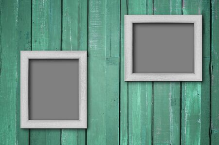 Two white wood picture frame on Green color paint plank wall for background
